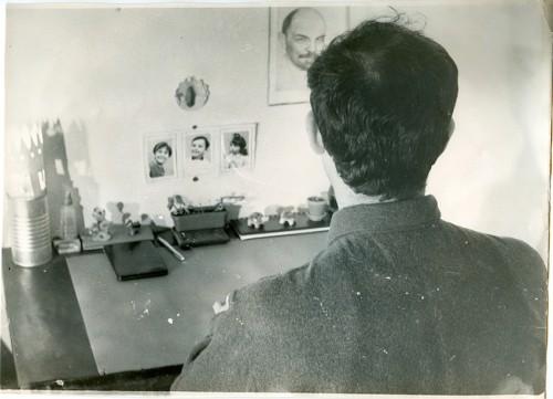 Sadek Hadjerès, photographie prise par un camarade en clandestinité en 1967, rue de Mulhouse. La photo, prise de dos, pour des raisons de sécurité, est destinée à être envoyée à la famille. En face, les photographies des enfants, et le portrait de Lénine, Archives privées ©Inas éditions.